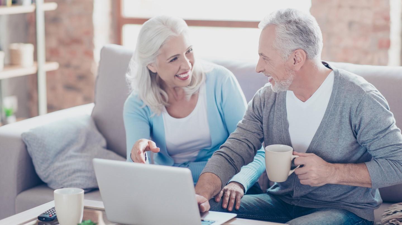 Bei Laune bleiben: Ein älteres Paar sitzt lachend vor einem Computer.